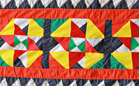 sewn: The Linangkit patern: Emboidery of the Dusun Lotud. Pieces of cloth sewn together in triangle pattern to make the linangkit pattern used to decorate wedding dias or traditioal costume.