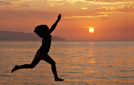 energetically: Silhouette of a young girl jumping energetically at the beach with golden sun setting at the background. Image is blurry due to selective focusing, contain visible noise and for background purposes only. Stock Photo