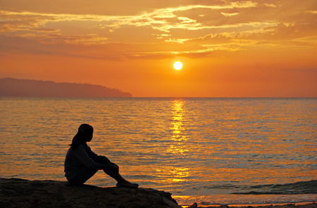 positive thinking: Young girl sitting on the rocks an watching the sun goes down in a golden hour. Image is blury due to selective focusing and shallow dept of field and suitable for background purposes only. Stock Photo