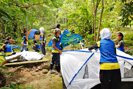 pitching: Kawang, Papar March 7, 2015 : A group of school girls working together pitching up tents for school extracurricular activity at  Kawang camping site.
