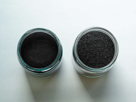 Activated carbon powder for a cosmetic face mask in two glass jars, top view on a white back