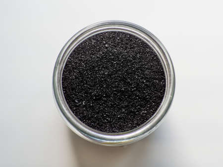 Activated charcoal powder for cosmetic face masks in a jar top view with copy space, white back