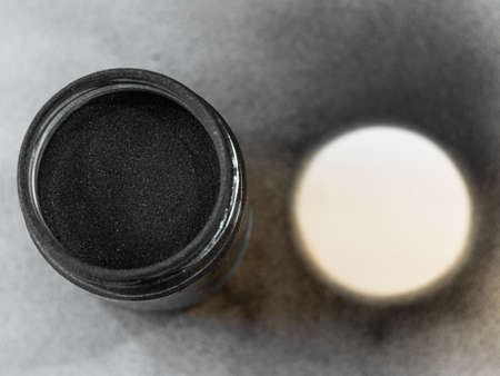 Activated carbon powder for cosmetic face mask in a jar, top view, black circle and white background