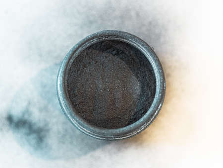 Activated carbon powder for cosmetic face mask in a jar, top view, blue shadow and white background