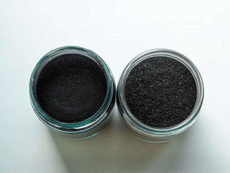 Activated carbon powder for a cosmetic face mask in two glass jars, top view on a white background