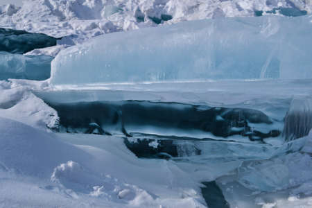 large iridescent crystal white blue ice floes with cracks shine in the light sun, Baikal Standard-Bild
