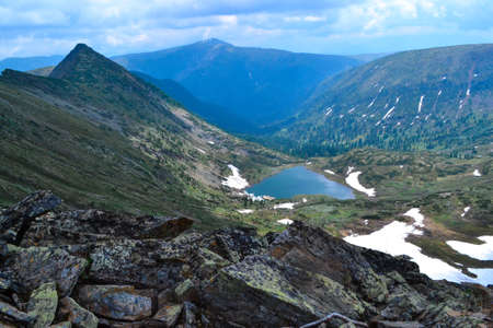 stones, view of mountain lake in form of heart among snow ice glaciers, green mountain ranges overgrown with trees, Chersky peak Banco de Imagens