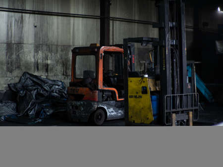 Red forklift truck on cement floor in front of hydraulic docking in coal departure area, transport truck in factory used to lift and move materials over short distance