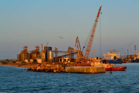 Coastal industrial factory with cranes and structures with port and transport ship. Generic view of industrial harbor with vessels docked in sunset light. Blue sea, gull