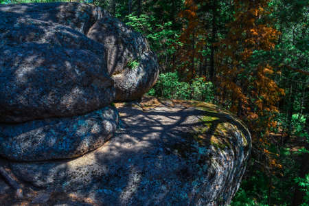 Textured rough orange stone rock covered with moss in light of sun with blue shadows from trees. Green red forest. Siberia
