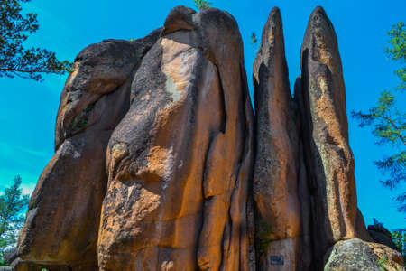Large stone red rocks vertically layered with crevices in the light of sun. Big tall textured rough rock is called Feathers. Natural park in Siberia. Krasnoyarsk pillars. Blue sky, summer
