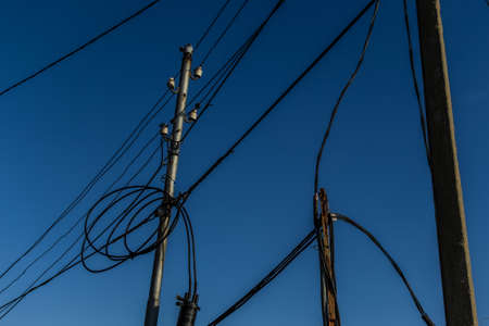 Power lines, electric poles with black wires on bright blue sky gradient backdrop