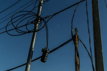 Power lines, electric poles with black straight and twisted wires on bright blue sky backdrop