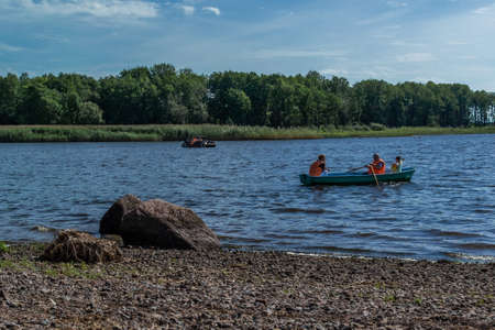 Two small passenger rowing paddle boats with people floats on bay of Baltic sea among green trees, forests in sunny weather. Stones coast. Russia summer