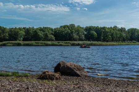 Small passenger rowing boat with people floats on bay of Baltic sea among green trees, bushes, forests in sunny weather. Pebbles shore with stones. Russia summer