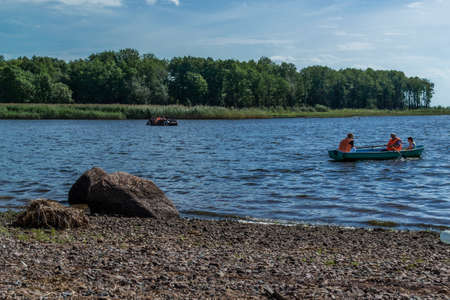 Small passenger rowing boats with family, people floats on lake in park among green trees, bushes, forests in sunny weather. Stones shore. Russia summer Banque d'images
