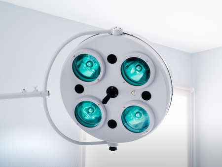 Round white swivel medical operating lamp with four green blue turquoise lights in doctor's office. White interier, window