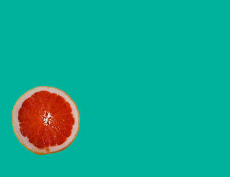 cut bright red orange half grapefruit slice on colorful turquoise light blue green background