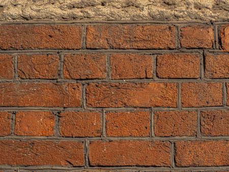 Brickwork made of red orange geometric horizontal bricks shine golden particles bonded with cement grout between square stones Reklamní fotografie