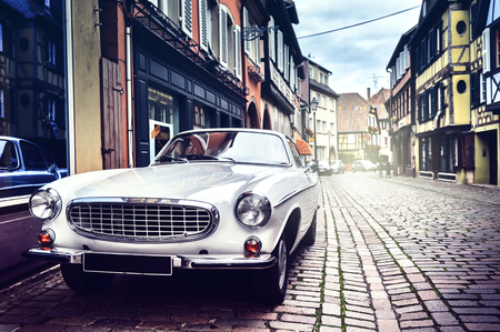 Retro car parked in old European city street