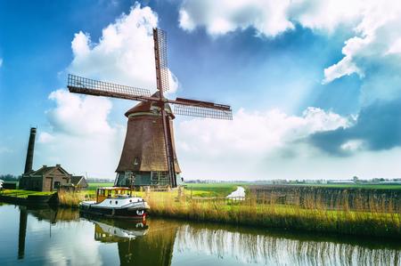 dutch: Traditional dutch windmill near the canal. Netherlands