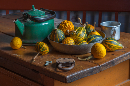 antique dishes: Village life. Composition with kettle, decorative pumpkin on a wooden table.