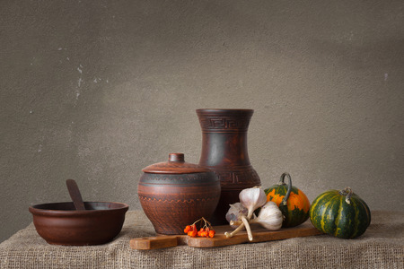 Still life in a rustic style: a set of pottery, pumpkin and garlic. Natural light from window.