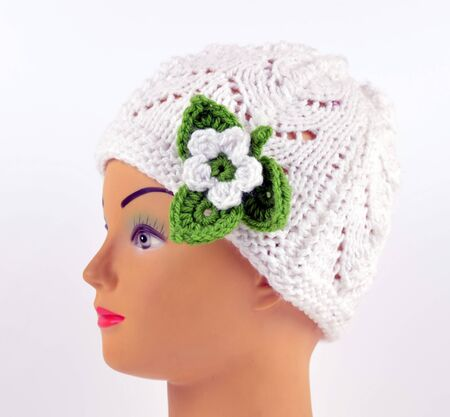 Knitted hat on head. White with green flower. Stock Photo
