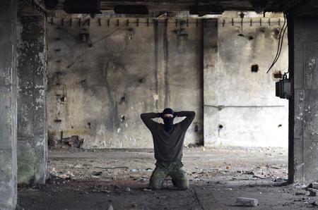 Masked man on knees, army theme