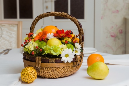 A basket with fruits and flowers on a restaurant table photo