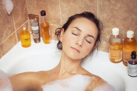 Young woman laying in bathtub full of foam photo