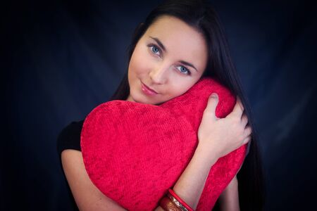 Woman with red heart shaped cushion on dark background photo