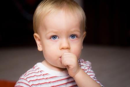 Baby boy sucking his thumb at home photo