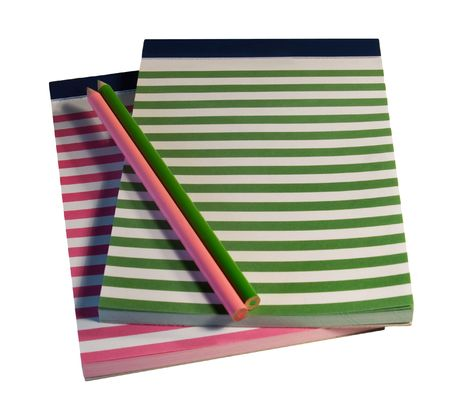 transcribe: Two fun striped notepads - one pink with white and the other green with white - with matching colored pencils, isolated. Stock Photo