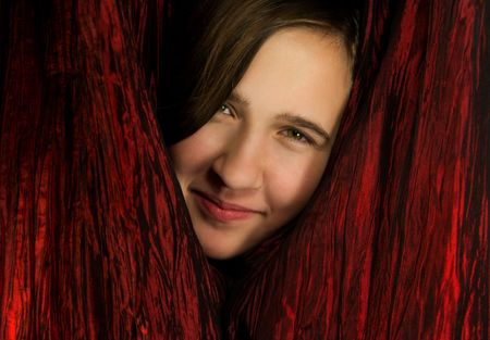 A smiling teen girl peers from between red curtains photo