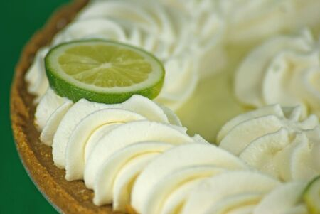 dollop: Close-up of a Key Lime Pie with whipped cream and lime slices.