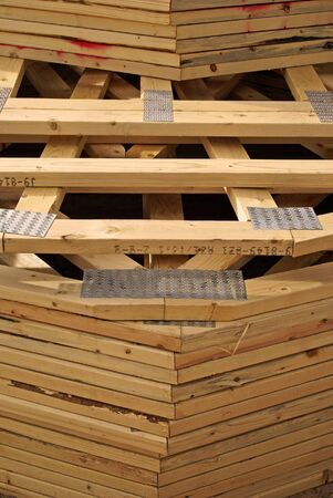 roof framing: A stack of wooden roof trusses to frame a new house being built, as delvered to the construction site.