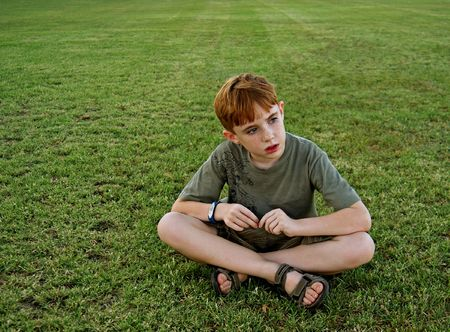 sandal: An 8-year-old boy sits on a grassy field and looks off out of frame Stock Photo