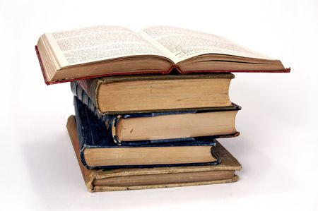 Pile of antique books, with one open on top of the stack
