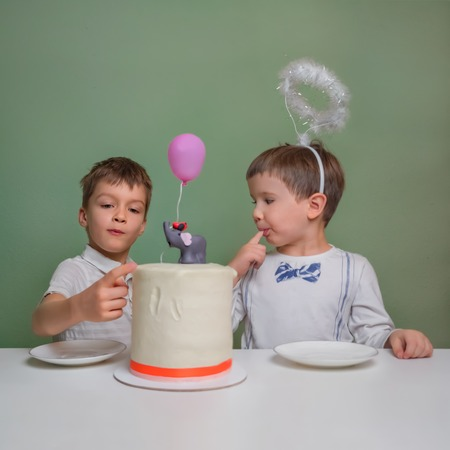 Two boys lick a cake cream. Two boys dressed in white eating birthday pie with hands. Birthday pie. Sweet table for children. Tasty food concept. Adorable little boys eating cake. Close-up