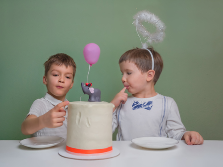 Two boys lick a cake cream. Two boys dressed in white eating birthday pie with hands. Sibligns Day celebration. Newborn sibling party celebration. 版權商用圖片
