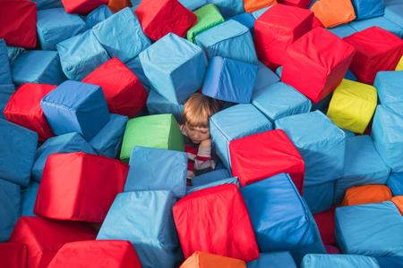 Autisme de l'enfant Psychologie de l'enfant conceptuel. Garçon recouvert de blocs mous colorés, cubes. Contexte de santé physiologique et psychologique des enfants. Enfant qui se remet du stress, maladie mentale.