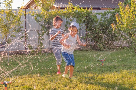 Summer activities. Children playing outdoor with automatic plant watering system. Smiling boy having fun outdoor. Water hoses watering the grass. laughter therapy. 写真素材
