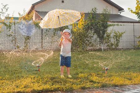 Attività estive. Bambini che giocano all'aperto. Ragazzo felice che gioca all'aperto con il sistema di irrigazione. Vacanze estive. Vacanze estive con bambini. Sfondo bambino felice. Emozioni positive del bambino.
