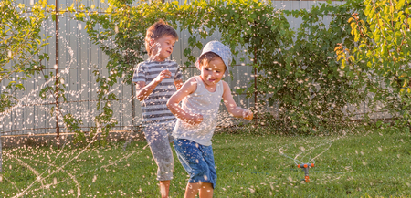 Happy children playing outdoor. Joyful siblings having fun on sunny summer day. Happy children playing outdoor. Positive emotions background. Summer time concept. Brothers playing together outdoor