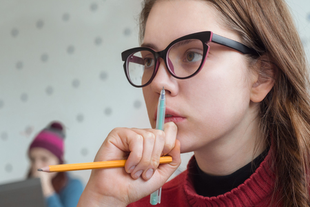 Thoughtful student at the university. Portrait of thinking female listening to lecturer, teacher, professor. Hipster girl learning, studying in creative atmosphere. Brain training. Smart girl portrait