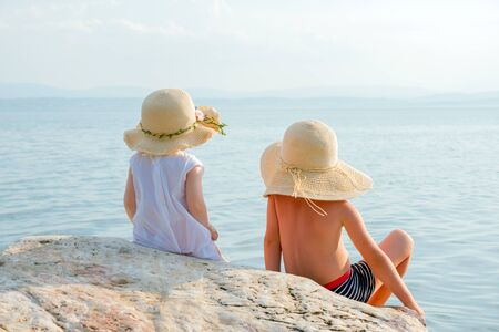 Little tourists near the sea. Vacation with children. Sunny summer days. Children on the seashore. Beautiful children looking to ocean. Happy childhood concept. Siblings, psyhology. Family vacation. Banque d'images - 129067806