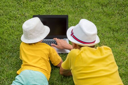 Father with son lying on the grass near laptop. Siblings and gadget outdoor. Father and son spending time together outdoor. Man with boy having fun on frontyard, backyard. Gadget and children