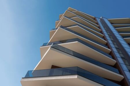 Modern highrise skyscraper steel and glass architecture. Architecture building with shifted corner balconies. Luxury house, residential apartments in modern style. Shopping center exterior.