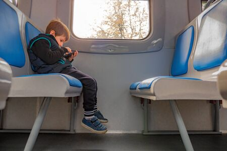 Boy with mobile phone sitting in train. Children and technologies. Young boy playing game on phone while sitting in train. Quality of internet connection. Young traveler travels with electronic map